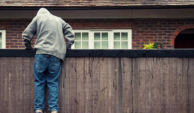Burglar climbing over a fence