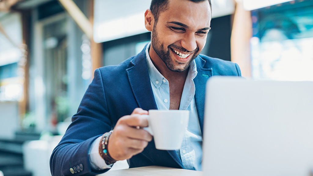 Smiling man on laptop with hot drink